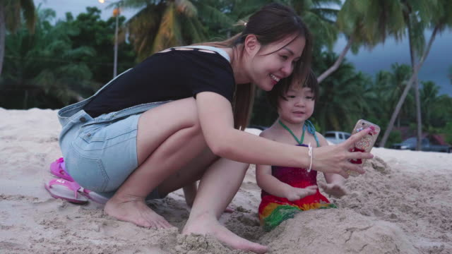 young mother and her daughter taking selfie with smart phone on the beach - baby girls stock videos & royalty-free footage