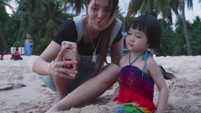 young mother and her daughter taking selfie with smart phone on the beach - photographing stock videos and b-roll footage
