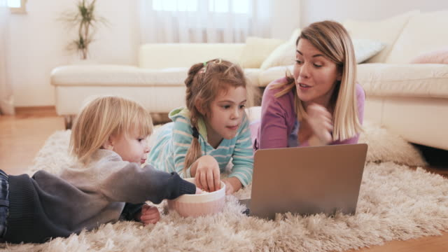 Young mother and her kids watching cartoons on laptop while relaxing on the carpet and eating popcorn.
