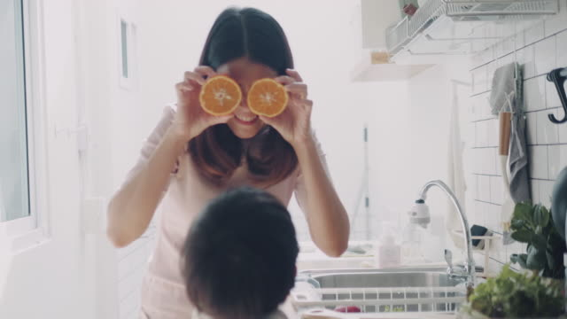 young mother and her little baby boy making a salad at home. - meal preparation stock videos & royalty-free footage