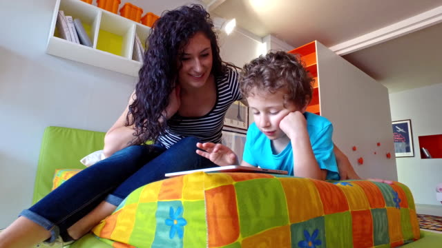 Giovane madre e il suo ragazzino utilizzando tavoletta digitale