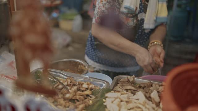 vídeos y material grabado en eventos de stock de joven madre y su hijo comprando fideos en el mercado de comida callejera en tailandia - comida china