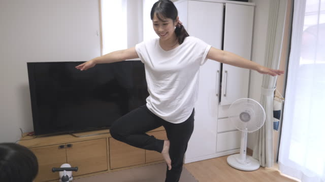 young mother and her son standing on one leg in living room - on one leg stock videos & royalty-free footage