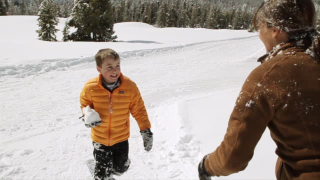 MS PAN SLO MO Young mother and son having fun and snowball fight out on beautiful winter's day / Sun Valley, Idaho, United States