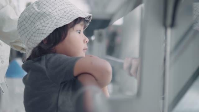 vídeos de stock, filmes e b-roll de matriz e filho novos que observam o sol que brilha na pista de decolagem no aeroporto - bebês meninos