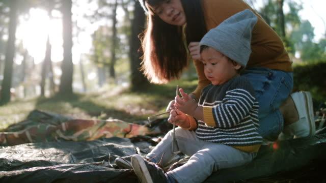 若い母親と息子息子のテントをセットアップする方法を教える - キャンプする点の映像素材/bロール
