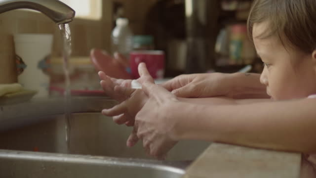 young mother and son washing hands in kitchen sink - washing hands stock videos & royalty-free footage