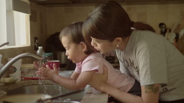 vídeos de stock, filmes e b-roll de jovem mãe e filho a lavar as mãos na pia da cozinha - washing