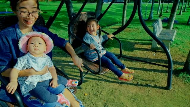 Joven madre y dos hijas descansar y disfrutar de una naturaleza en silla del oscilación en el Parque