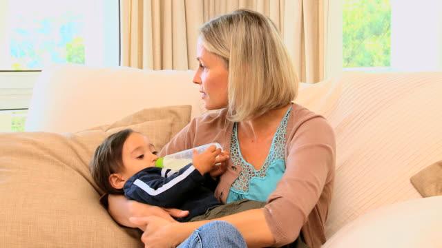 vídeos de stock e filmes b-roll de young mother bottle-feeding baby on sofa / cape town, western cape, south africa - vida de bebé