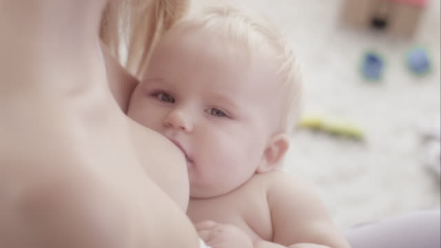 Young mother breast-feeding her baby. Close up