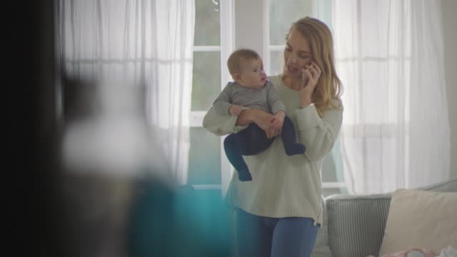 vidéos et rushes de young mother carrying child answers and talks on smartphone in home living room. - répondre