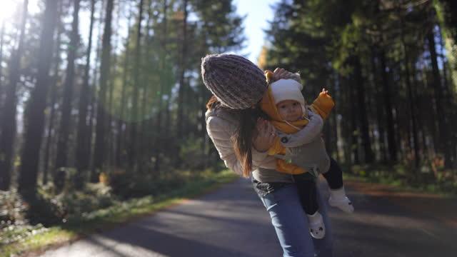 giovane madre portando il suo bambino in baby carrier e giocare con lei mentre in piedi sulla strada in natura - stare in piedi video stock e b–roll