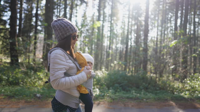 young mother carrying her baby in baby carrier and walking through forest on sunny day - carrying stock videos & royalty-free footage