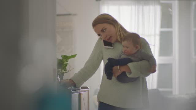 young mother carrying small child talks on smartphone and writes in notebook. - husinteriör bildbanksvideor och videomaterial från bakom kulisserna