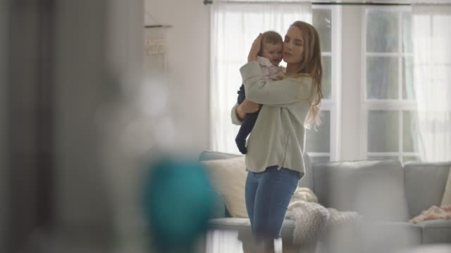 young mother comforts child in home living room. - residential building stock-videos und b-roll-filmmaterial