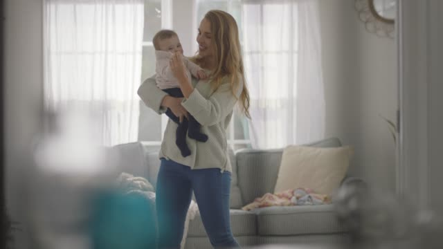 slo mo. young mother dances with her baby in home living room. - family with one child stock videos & royalty-free footage