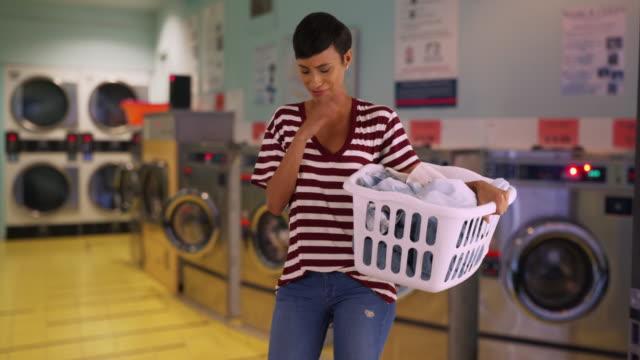 young mother doing the laundry sneezes - tvättmedel bildbanksvideor och videomaterial från bakom kulisserna