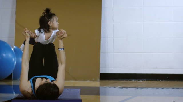 Young mother exercising with baby in gymnasium