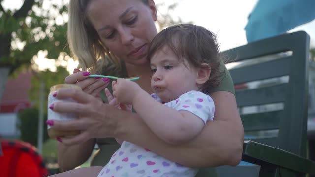 young mother feeding a baby girl outdoors in summer - dependency stock videos & royalty-free footage