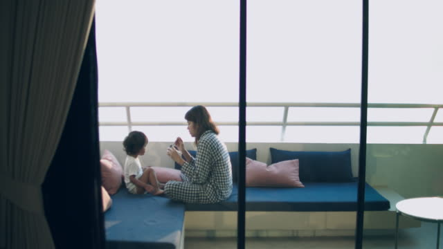 vidéos et rushes de jeune maman nourrir son bébé (2 ans) dans le salon - céréale