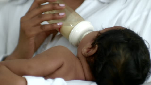 young mother feeding her baby with a bottle - torso stock videos & royalty-free footage