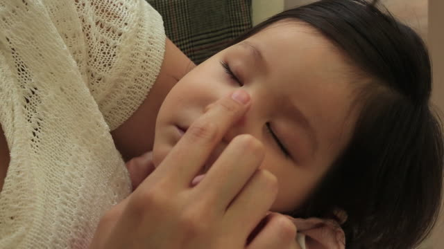 young mother gently stroking nose of her sleeping baby - 女の赤ちゃん点の映像素材/bロール