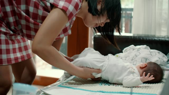 vídeos y material grabado en eventos de stock de joven madre vestirse de su bebé niño(0-1 meses) - 0 1 mes