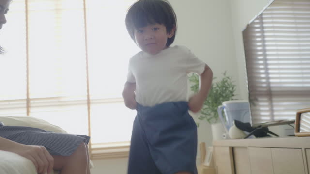 young mother getting dressed up a son. - trousers stock videos & royalty-free footage