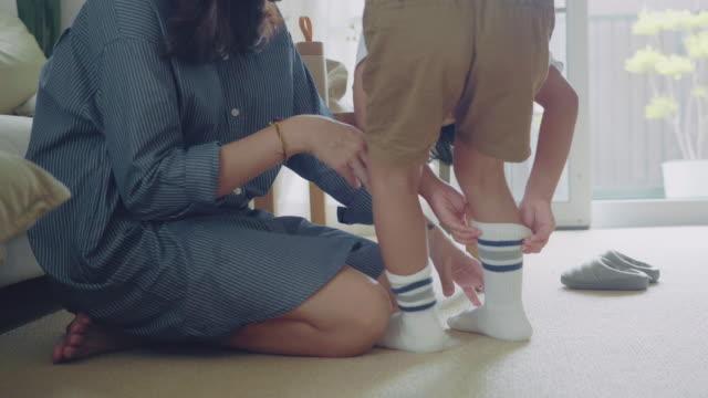 vidéos et rushes de jeune mère s'habillant vers le haut d'un fils. - cartable