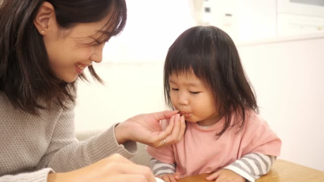 young mother giving grape to her little daughter - straight hair stock videos & royalty-free footage