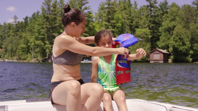 Young mother helping her daughter put lifejacket on in boat