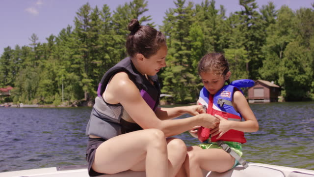 young mother helping her daughter put lifejacket on in boat - life jacket stock videos & royalty-free footage