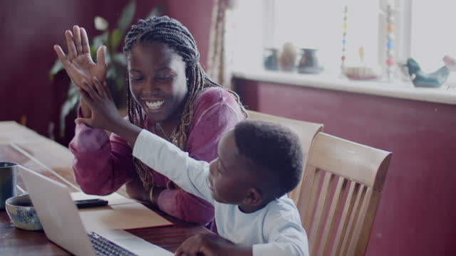 young mother helping her son with his school work - one parent stock videos & royalty-free footage