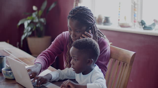 young mother helping her son with his school work - braided hair stock videos & royalty-free footage