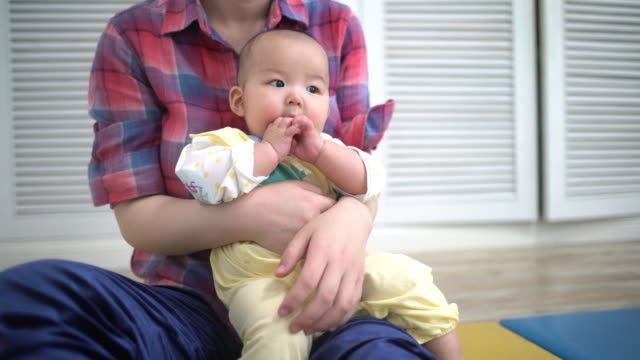 vidéos et rushes de young mother holding 6 months baby girl - 6 11 mois