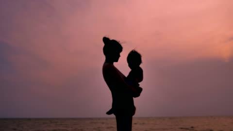 ung mamma innehav baby på stranden silhuetten - silhuett bildbanksvideor och videomaterial från bakom kulisserna