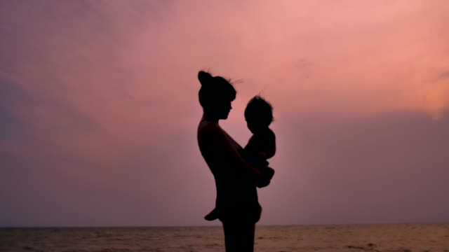 young mother holding baby on the beach silhouette - stringere tenere video stock e b–roll