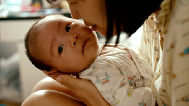 young mother holding her baby in her arms and kissing - 0 1 months stock videos & royalty-free footage