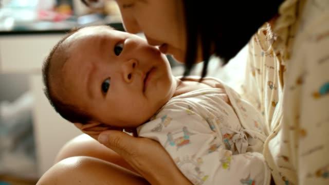 vídeos y material grabado en eventos de stock de joven madre sosteniendo a su bebé en sus brazos y besando - 0 1 mes