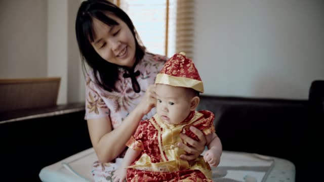 young mother holding her baby son in chinese new year festival - baby clothing stock videos & royalty-free footage