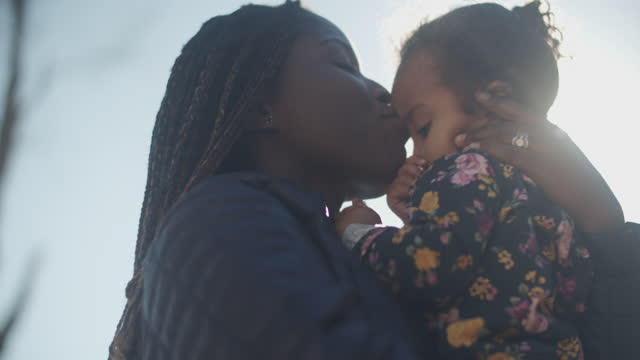 cu young mother holding her daughter outdoors - braided hair stock videos & royalty-free footage