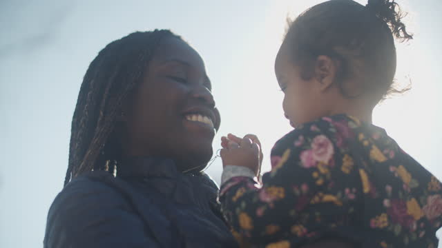 cu young mother holding her daughter outdoors - baby girls stock videos & royalty-free footage