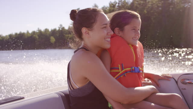 Young mother holding her daughter while enjoying a boat ride