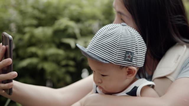 junge mutter hält ihren sohn und mit smartphone-videoanruf - 6 11 months stock-videos und b-roll-filmmaterial
