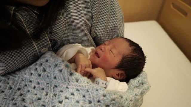 病院で生まれながらの赤ちゃんを抱いた若い母親 - 愛情豊か点の映像素材/bロール