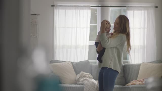 slo mo. young mother holds her baby in home living room. - living room点の映像素材/bロール