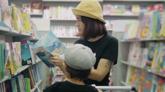 young mother is choosing a book with her son. - bookstore stock videos & royalty-free footage
