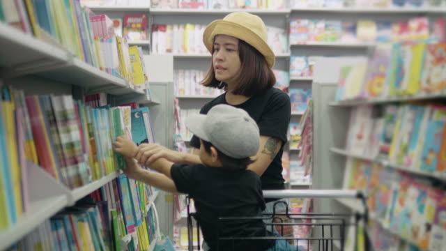 stockvideo's en b-roll-footage met jonge moeder is het kiezen van een boek met haar zoon. - prentenboek