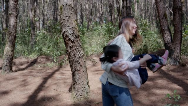 vidéos et rushes de jeune mère levage petite fille dans l'air sur le parc - famille monoparentale